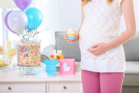 Pregnant woman holding cupcake at baby shower party, indoors