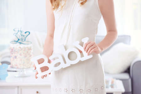 Pregnant woman holding decor for baby shower party, indoors
