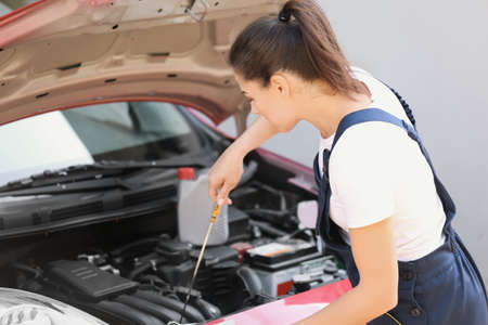 Young mechanic checking car engine oil level outdoors