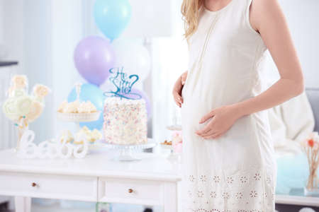 Pregnant woman at baby shower party, indoors