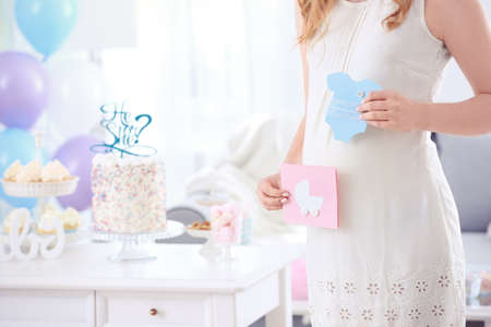 Pregnant woman holding cards for baby shower party, indoors Banque d'images - 98947399