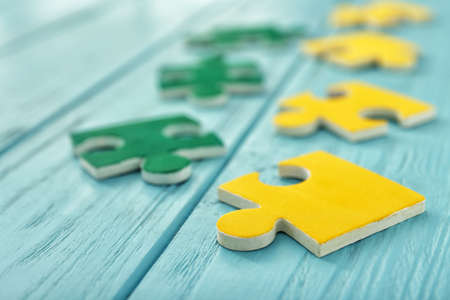 Color puzzles on wooden table Stock Photo