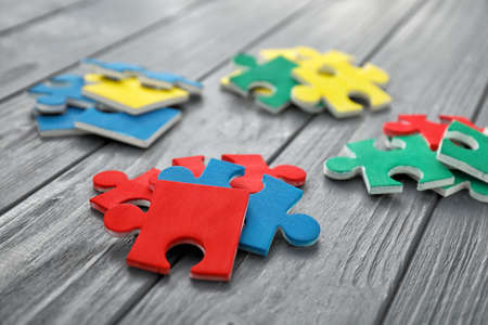 Color puzzles on wooden background Stock Photo
