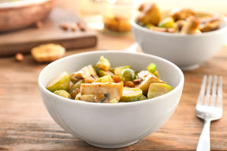 Bowl with yummy brussel sprouts salad on wooden table Stock Photo