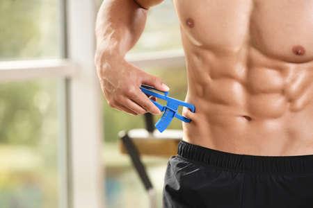 Muscular young man using body fat caliper in gym