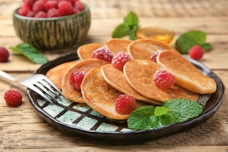 Plate with tasty buckwheat pancakes on table