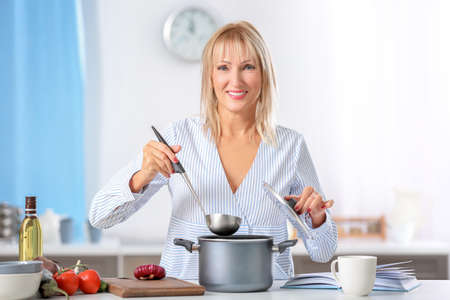 Beautiful mature woman cooking in kitchen
