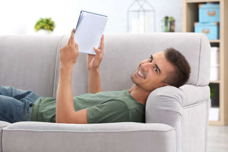 Young man reading book on sofa at home