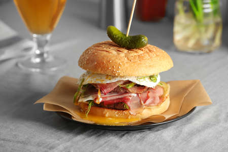 Tasty burger with prosciutto and egg on table