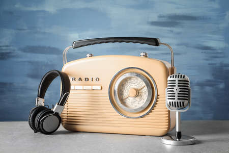 Retro radio, microphone and headphones on table against blue wall