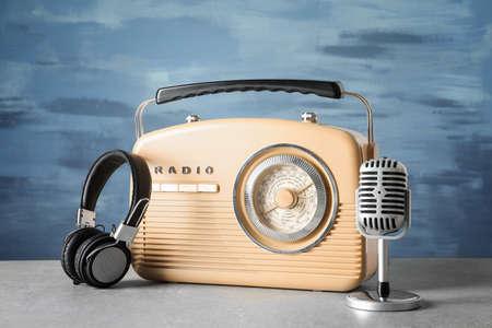 Radio retro, micrófono y auriculares en la mesa contra la pared azul