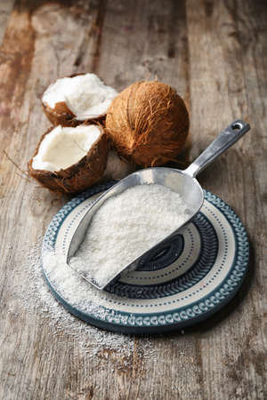 Desiccated coconut in scoop on wooden table