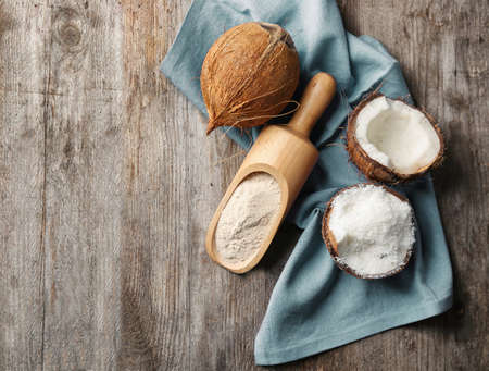 Scoop with flour and desiccated coconut in nut on wooden table