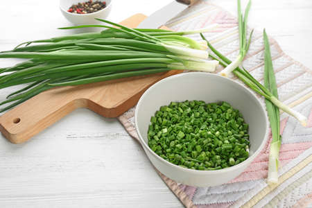 Bowl with fresh green onion on table Stock Photo