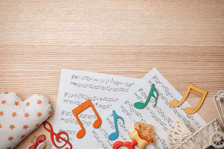 Beautiful composition with music sheets on wooden background. Baby songs concept