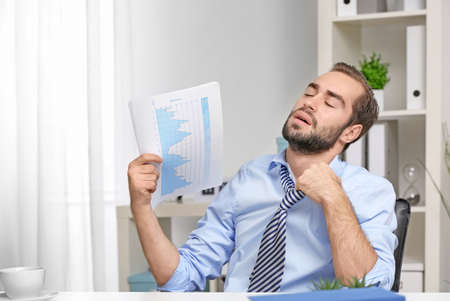 Young man feeling hot in office Stockfoto - 99482474