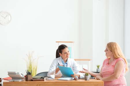 Jonge vrouwelijke arts die te zware vrouw in kliniek raadpleegt Stockfoto