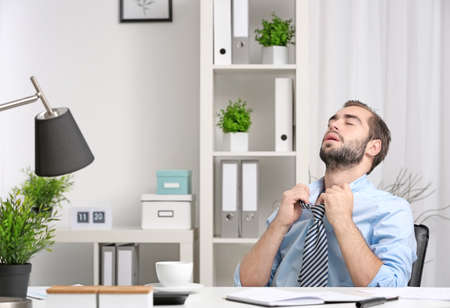 Young man feeling hot in office
