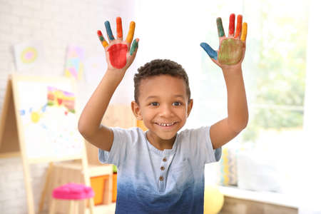 Little African-American boy with painted hands indoors