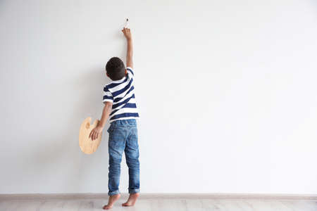 Little African-American boy painting on wall indoors