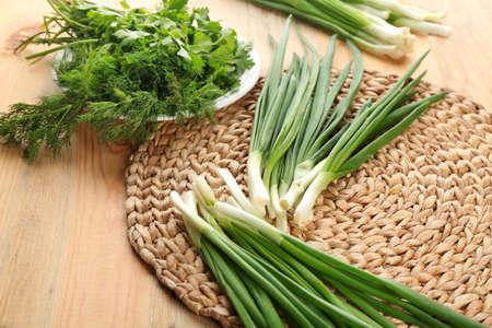 Fresh green onion on wicker mat Stock Photo