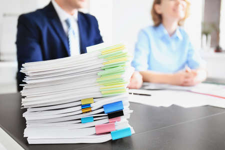 Stack of documents on table and blurred workers in office