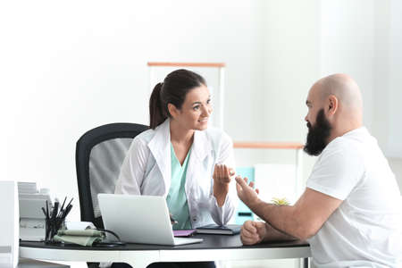 Young female doctor consulting overweight man in clinic