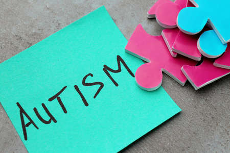 Composition of different puzzles and sticker with word AUTISM on grey background