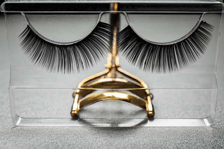 Curler and false eyelashes on table Stock Photo