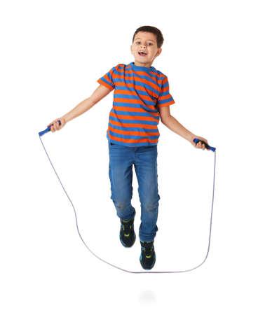 mignon petit garçon jouant avec saut de corde sur fond blanc