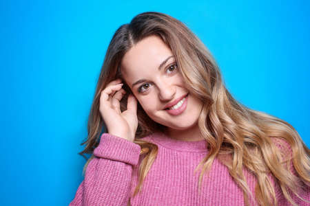 Young smiling woman on color background Stock Photo