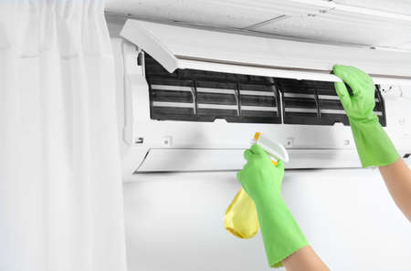 Young woman cleaning air conditioner at home
