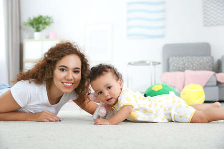 Cute baby and mother lying on floor at home