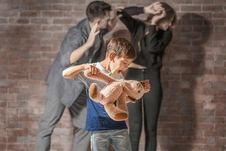 Kleine jongen straffen teddybeer terwijl ouders vechten op de achtergrond