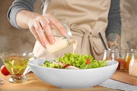 Vrouw die smakelijke saus toevoegen aan salade in schotel op lijst Stockfoto