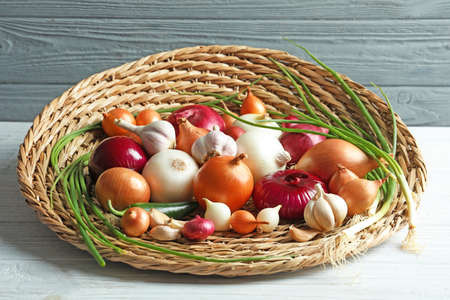 Wicker tray with different onions on wooden table
