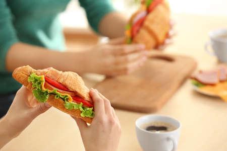 Woman holding delicious croissant sandwich, closeup