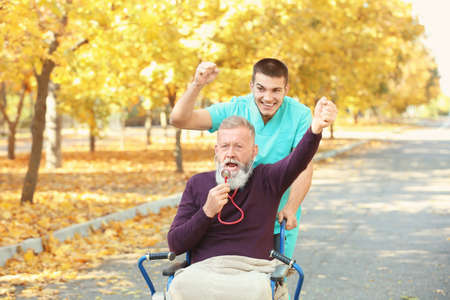 Young caregiver walking with senior man in park Stock Photo