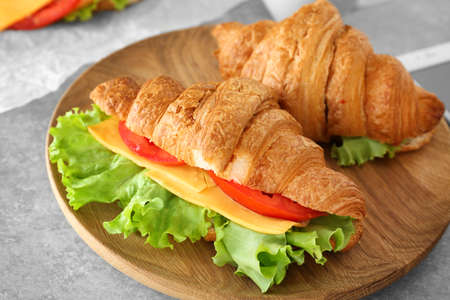 Plate with delicious croissant sandwiches on table