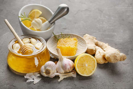 Composition with honey and garlic as natural cold remedies on grey textured background Stock Photo