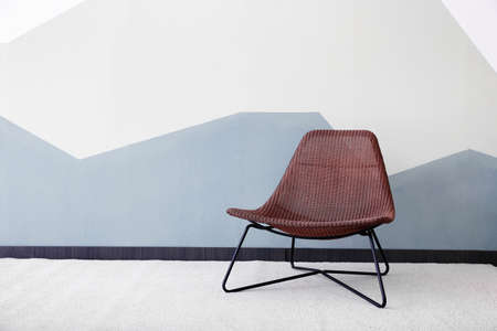 Stylish armchair against color wall background