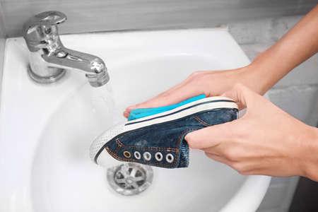 Woman washing sneaker with rag in sink, closeup