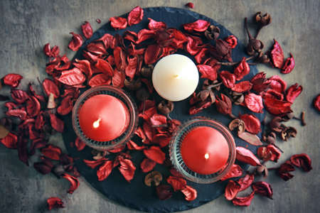 Composition with burning candles and dried flower petals on table Stock Photo