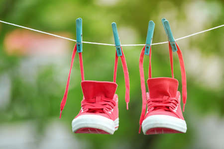 Pair of red sneakers hanging on clothesline outdoors