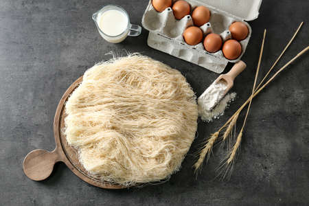 Shredded thin dough with ingredients on table