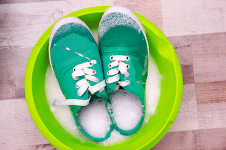 Pair of turquoise sneakers in plastic basin with suds on floor Stock Photo
