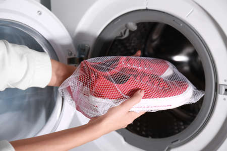 Woman putting mesh with red sneakers into washing machine, closeup