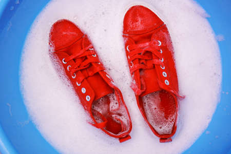 Pair of red sneakers in plastic basin with suds, closeup