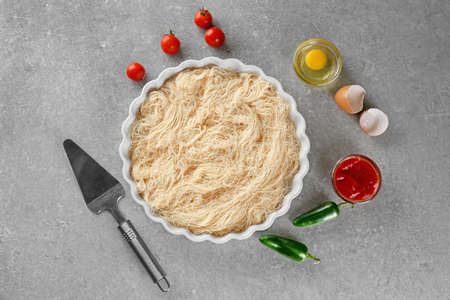 Baking dish with shredded thin dough on table