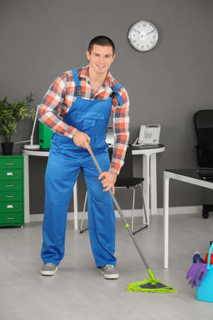 Young man washing floor with mop in office
